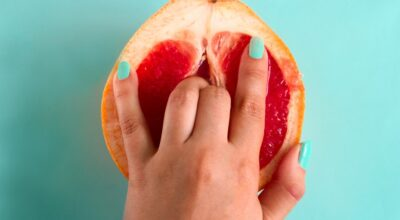 two-fingers-in-a-grapefruit-isolated-on-a-blue-background-top-view-sex-concept-art-attractive-beauty_t20_B8NXaj